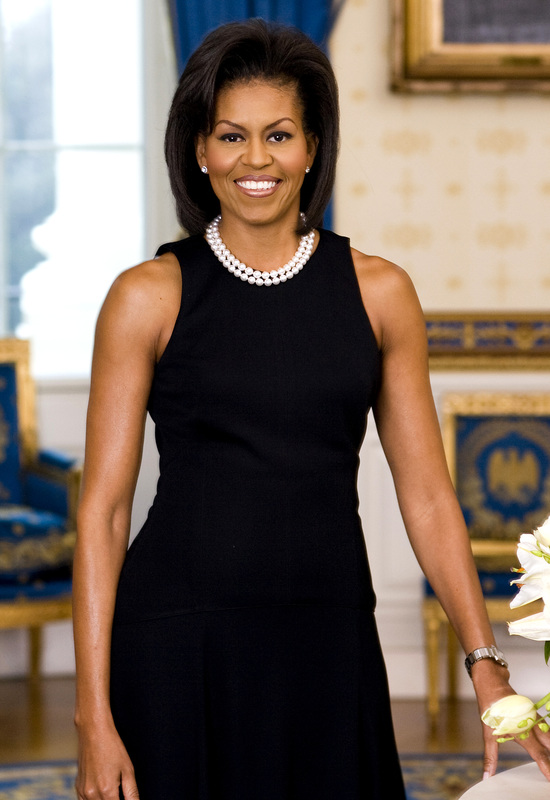 Michelle Obama standing in a black dress.
